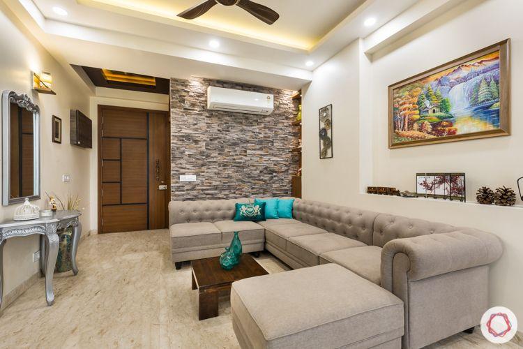 Beige sofa-stone clad wall-antique dresser