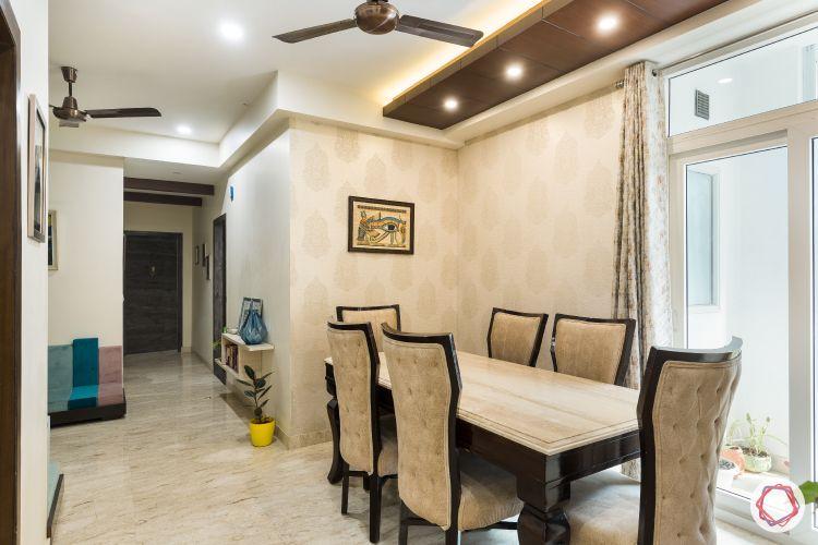 Livspace noida-wooden ceiling-beige wallpaper-golden motifs-marble topped table