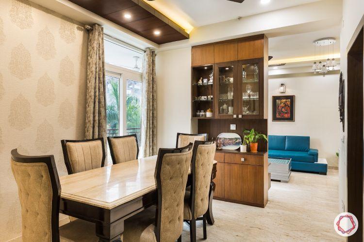 Livspace noida-wooden ceiling-beige wallpaper-golden motifs-marble topped table-wooden crockery unit