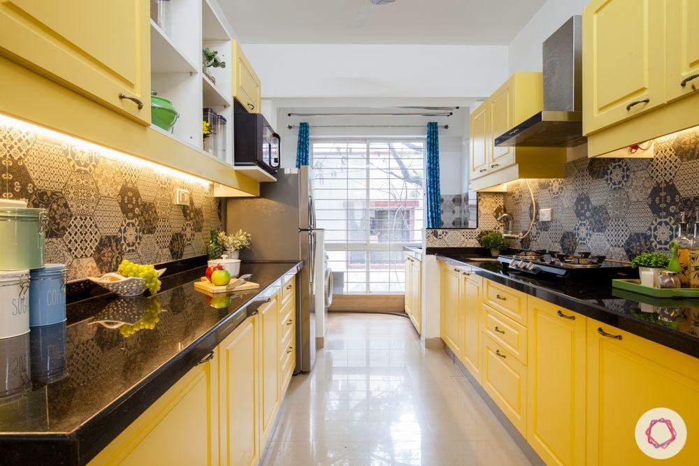 yellow-cabinets-grey-backsplash-black-countertop-profile-lights