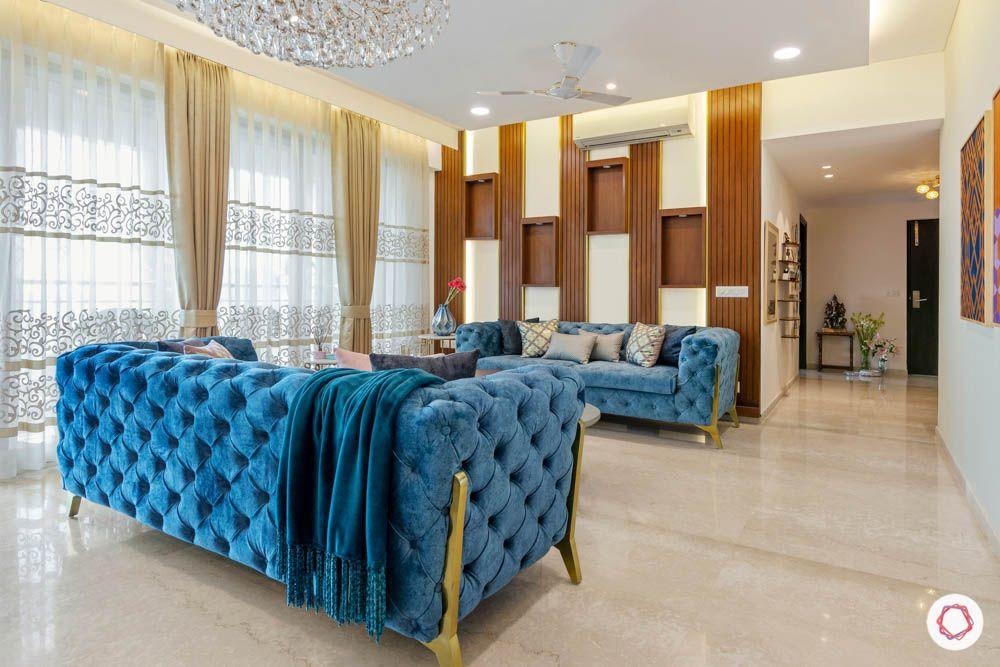 jewel toned interiors-blue sofa-chandelier type-wood display unit