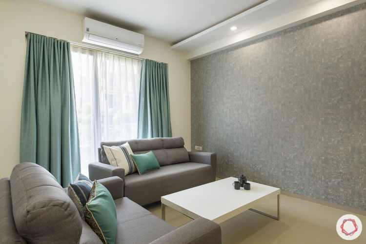 3 bhk apartment-grey textured wallpaper-grey sofa-marcel center table-blue curtains