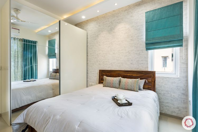 3 bhk apartment-master bedroom-exposed brick wallpaper-wooden bed-sliding wardrobe-mirror door
