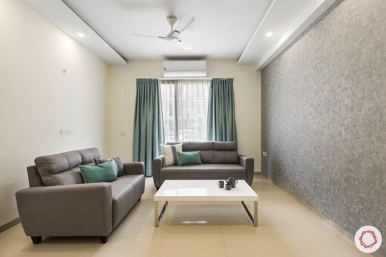grey textured wallpaper-grey sofa-marcel center table-blue curtains-false ceiling