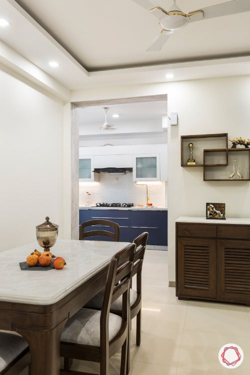 dining room-wooden furniture-upholstered-artwork-crockery unit-display shelves-false ceiling-kitchen