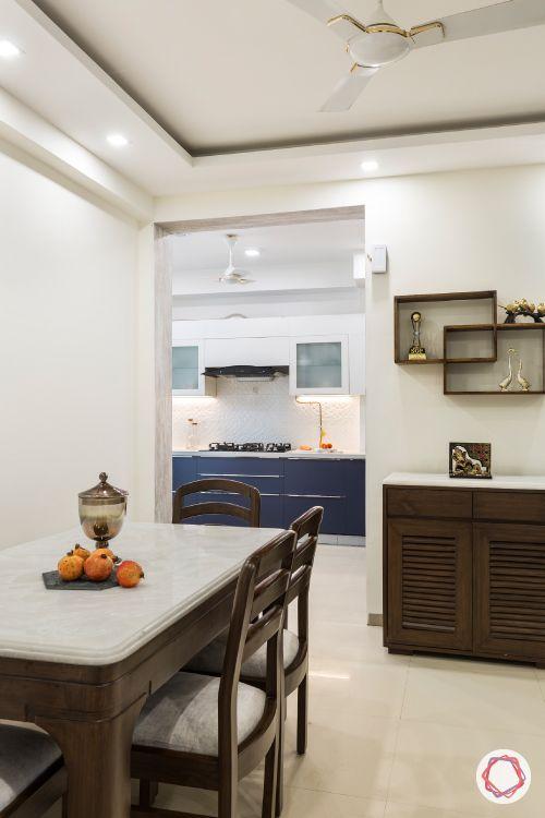 dining room-wooden furniture-upholstered-artwork-crockery unit-display shelves-false ceiling-kitchen