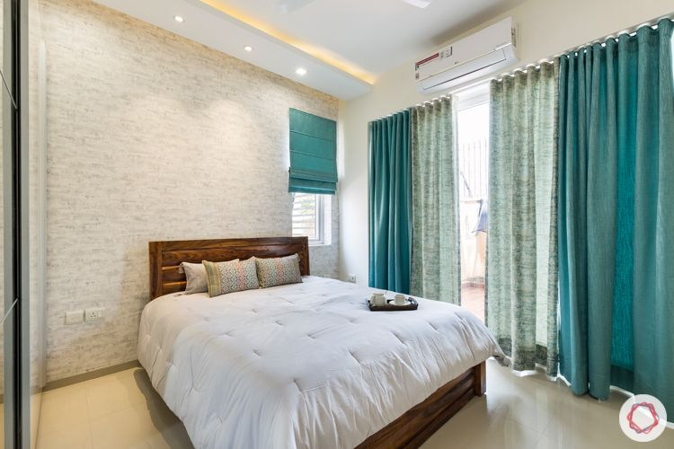 3 bhk apartment-master bedroom-exposed brick wallpaper-wooden bed-blue curtains