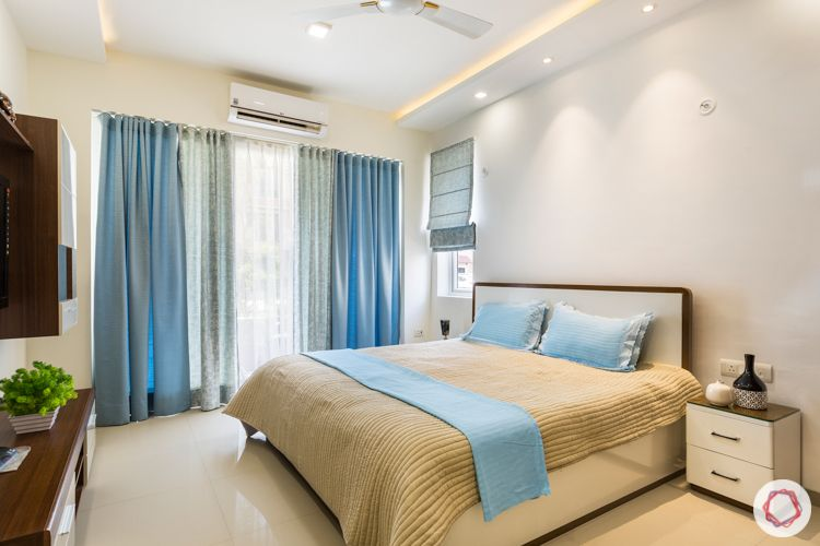 blue blinds-wooden bed-side table-tv unit-blue curtains