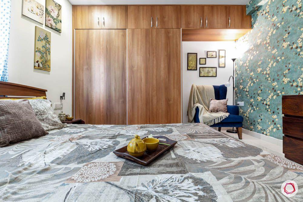 floral wallpaper-wooden wardrobe-blue arm chair