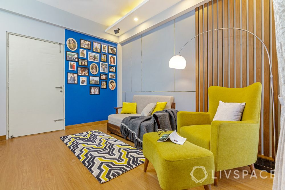 4 BHK flat design-yellow accent chair-rug-floor lamp-sofa-gallery wall-wooden panelling