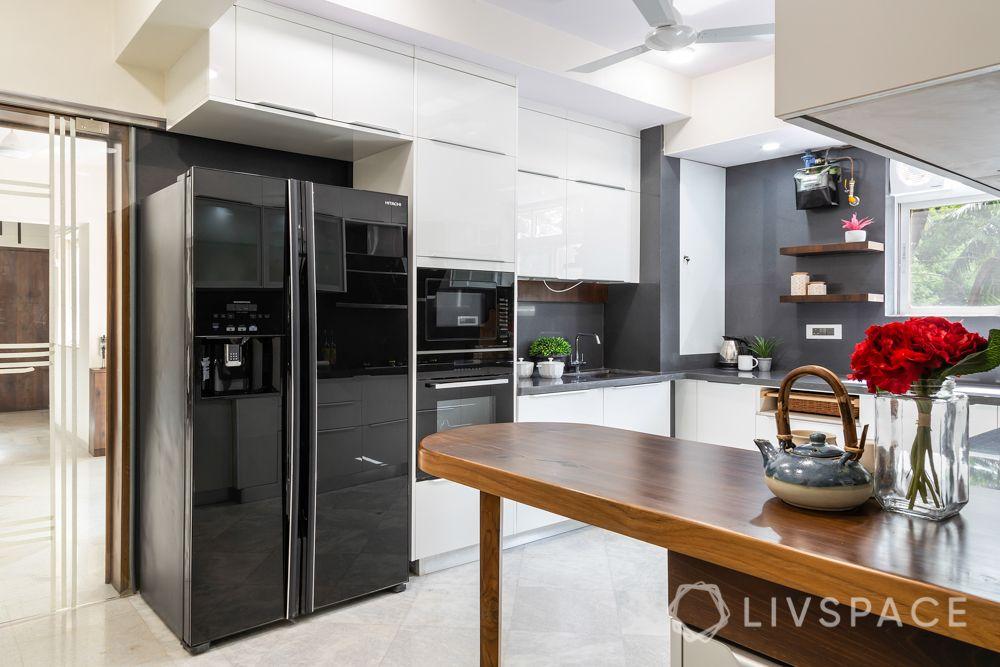 kitchen-renovation-interiors-in-Mumbai-breakfast-table-fridge-cabinets