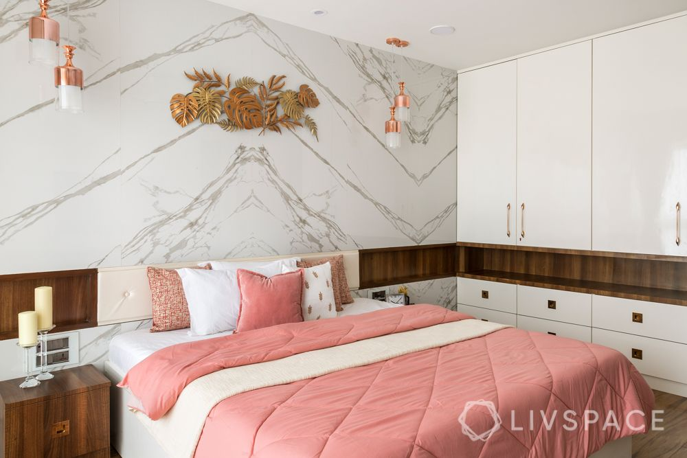 marble wall-hinged wardrobes-gold wall mount-pendant lights-pink bedded-wooden interiors