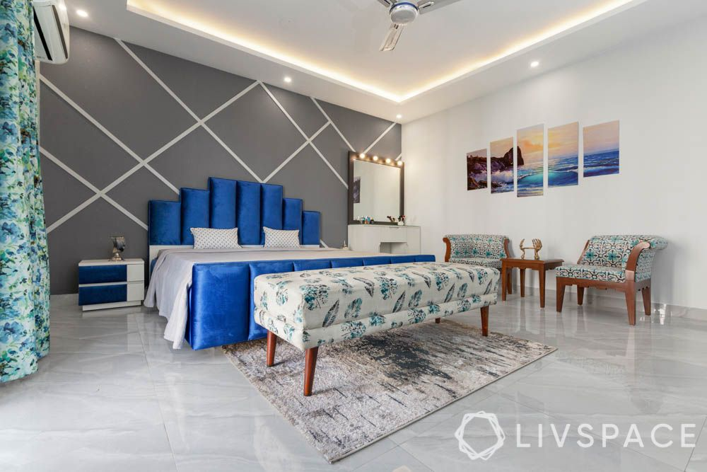 Gender neutral bedrooms for couples-grey textured wallpaper-blue velvet headboard-upholsterd furniture