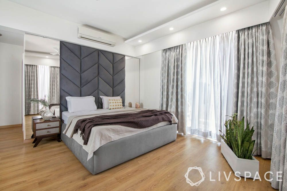 Gender neutral bedroom for couples-grey headboard-mirrors-wooden flooring-plants