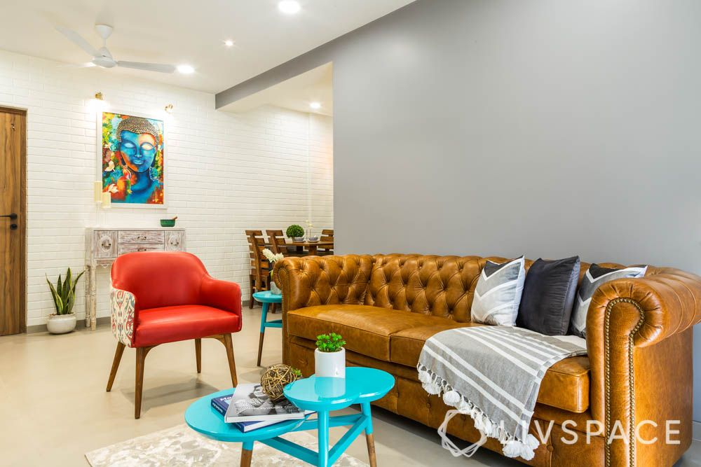 2bhk interior design-leather tufted sofa-red chair-blue coffee table