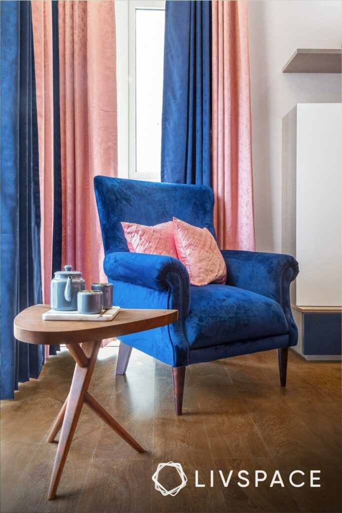 best flooring for house in india-blue chair-pink pillows-pink and blue curtains-wooden flooring-coffee table