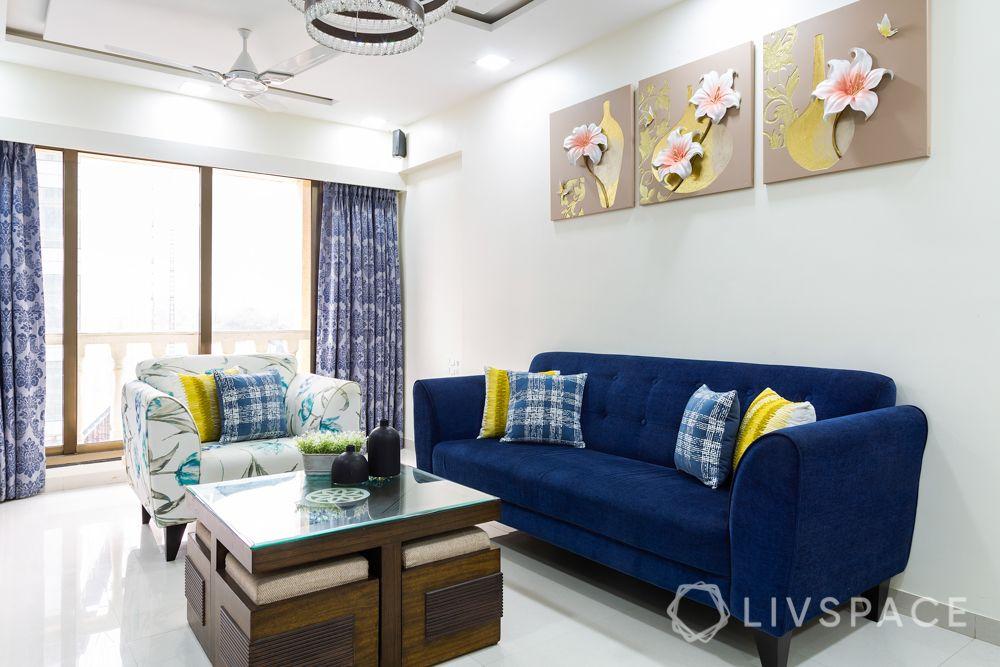 clean white walls-blue sofa-wall art-coffee table-blue curtains-printed armchair