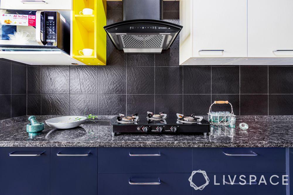 interior design firms in bangalore-textured black tile backsplash-membrane kitchen-yellow open unit
