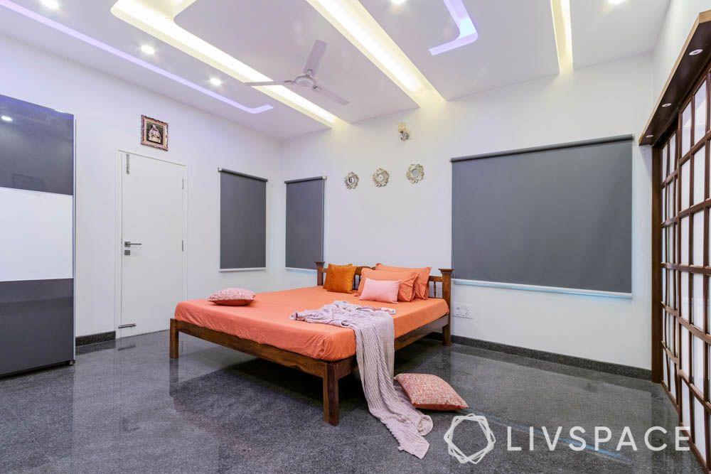 villa design-master bedroom-wooden bed-orange bedding-wooden rafters door-pop false ceiling
