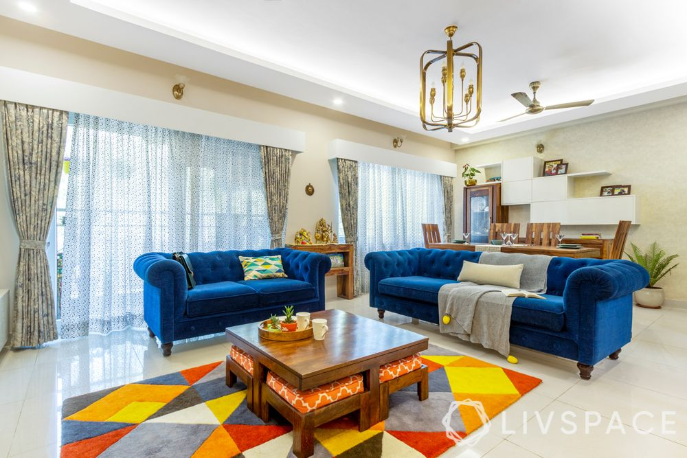 3 bhk home design-living room-blue sofa-coffee table-nested ottomans-carpet