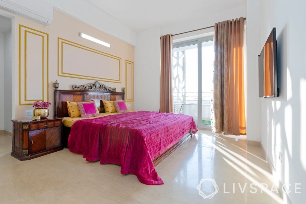 master bedroom-gold wall trims-carved wooden bed