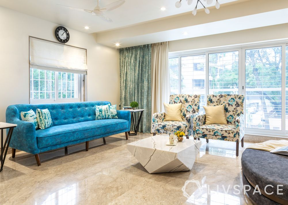 modern villa design-living room-blue sofa-floral armchairs-chandelier-marble tv unit