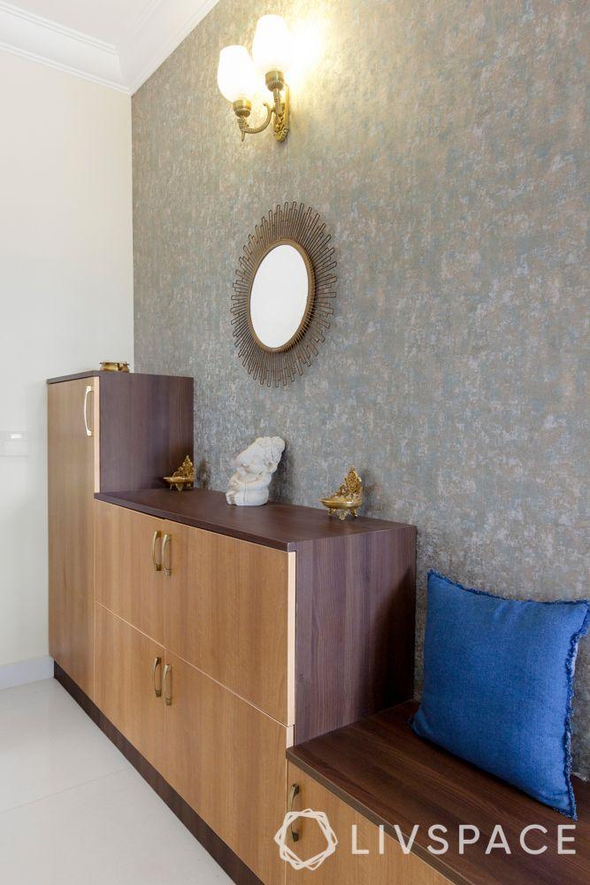 simple interior design-wooden shoe cabinet-brass lamps-mirror designs-sunburst mirror-grey wallpaper