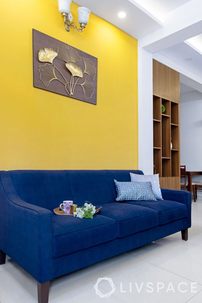 living room-yellow accent wall-blue sofa-laminate partition