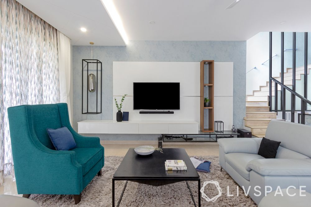 villa house design-blue armchair-tv unit design-coffee table-light blue sofa-textured wall paint