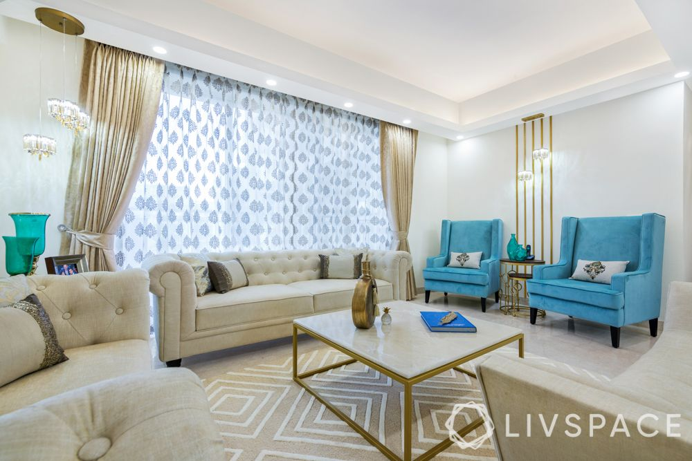 interior design company in gurgaon-living room--neutral sofa-pattern rug-gold wall trims-textured wallpaper