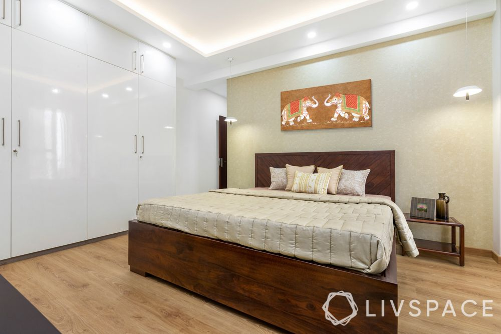 3 bhk design-laminate wardrobes-frosted white-hinged storage-wooden bed-gold wallpaper