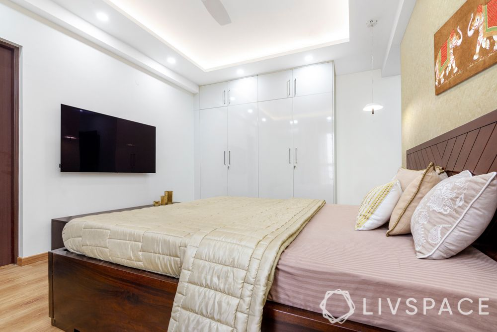 laminate wardrobes-frosted white-hinged storage-wooden bed-gold wallpaper