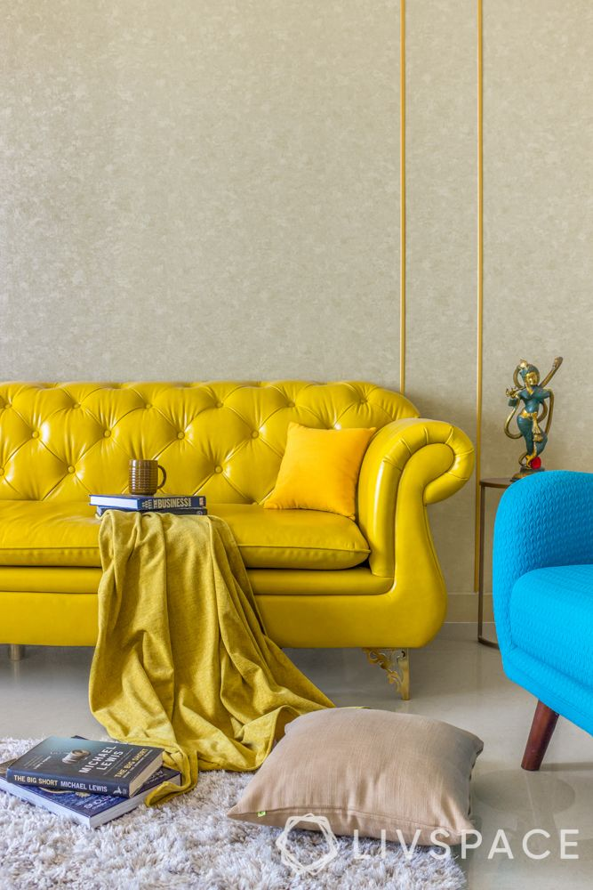 yellow tufted sofa-gold trims on wall