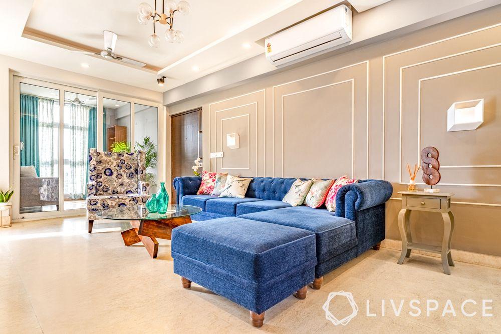 4BHK interior design-living room-L shaped blue sofa-wall trims