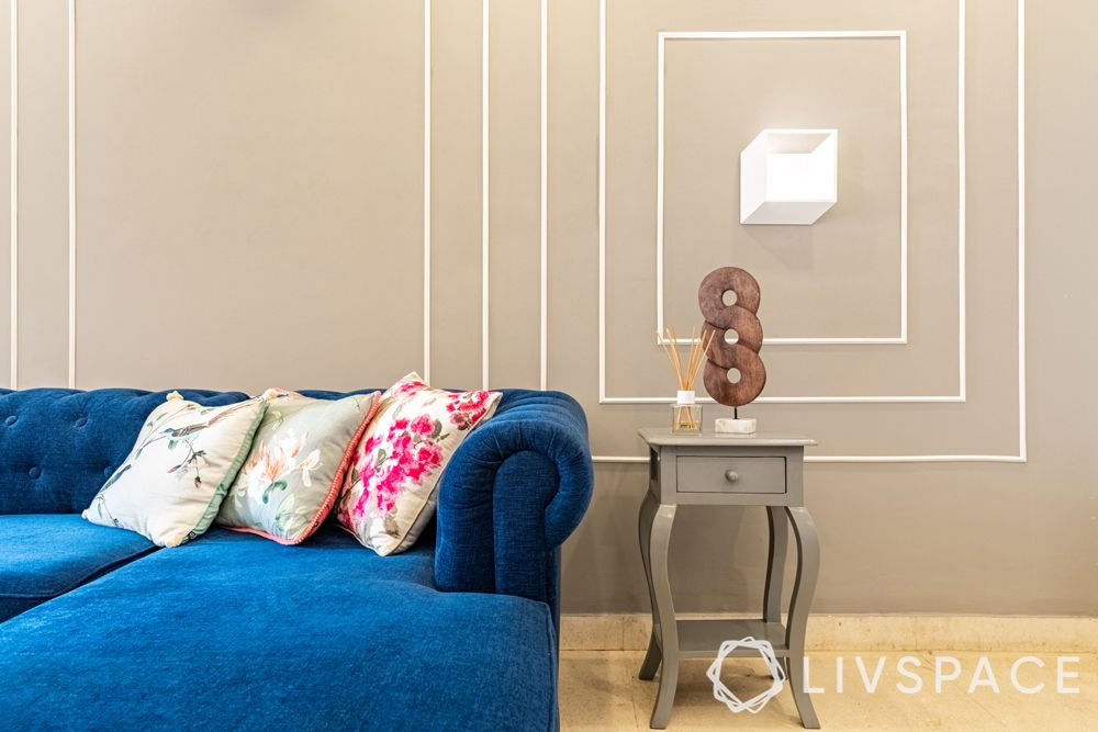 4BHK in Gurgaon-blue sofa-colourful cushions-side table