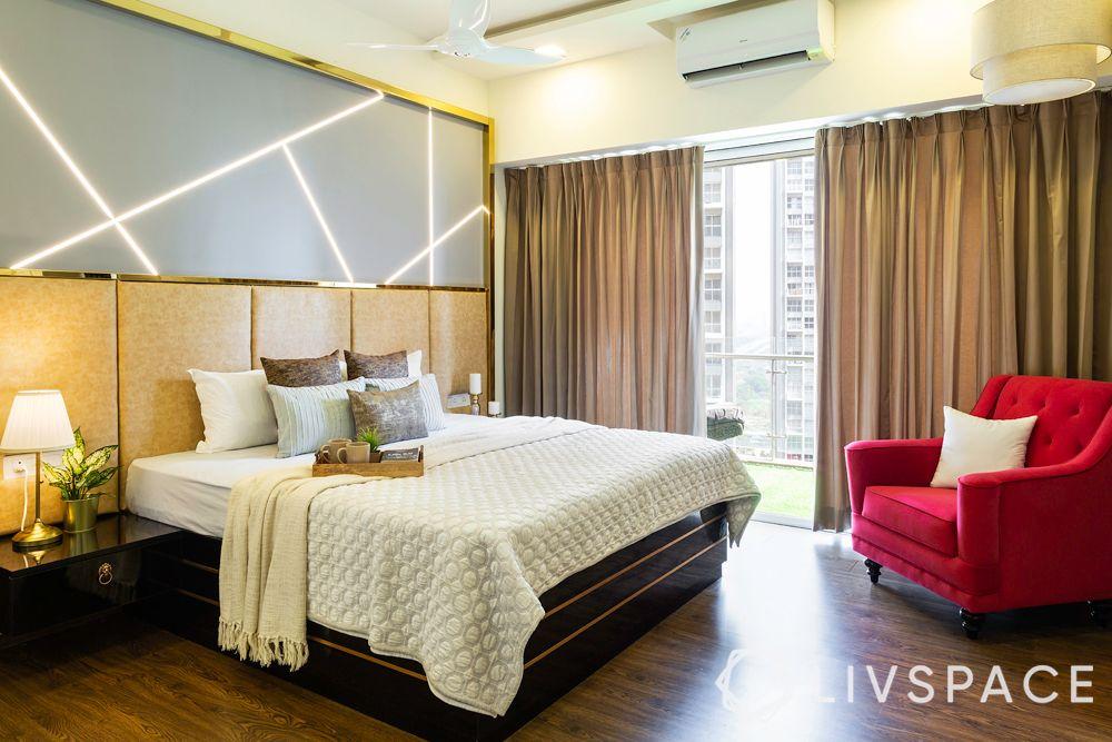 best interior designers-backlit headboard-red armchair