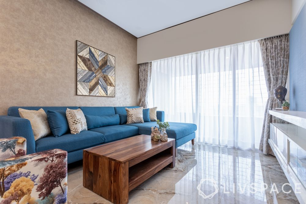 best home designers-living room-blue sofa-accent wall-centre table-flooring