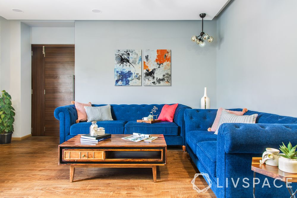 livspacehomes-low budget house-living room-blue sofa-wooden flooring-coffee table
