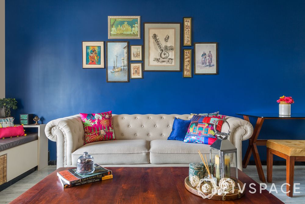 livspacehomes-low budget house-artsy indian living room-sofa-blue wall-wooden centre table
