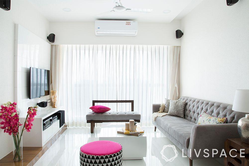 minimalist house-white interiors-grey sofa-pink pouffe