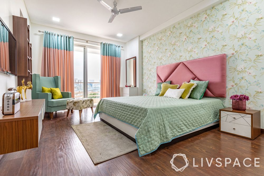 top interior designers in Delhi-pastel bedroom-floral wallpaper-dusty pink headboard-mint green accent chair