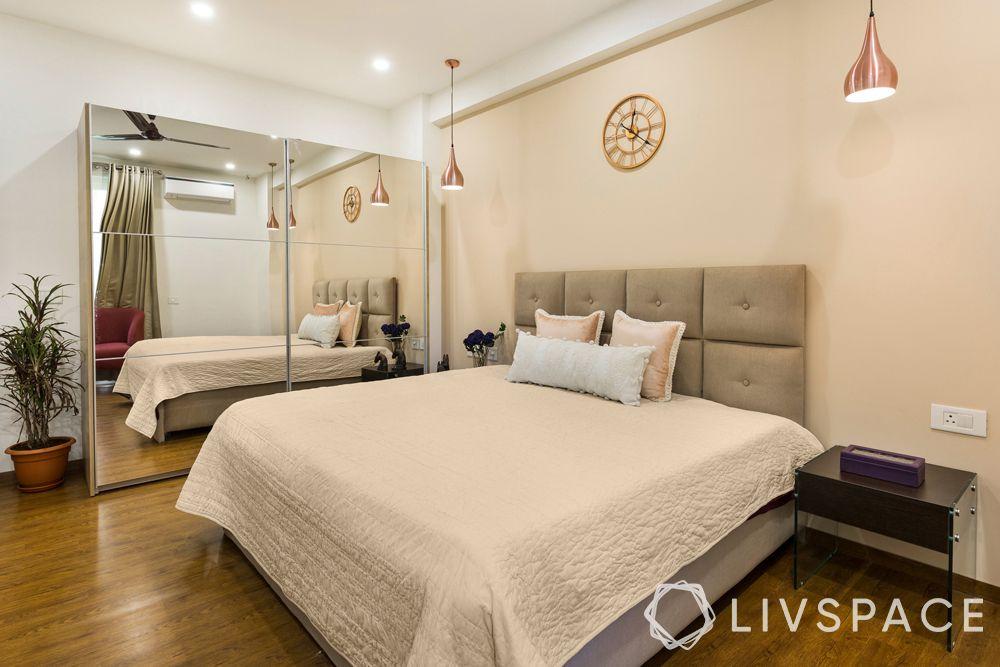 top interior designers in Delhi-beige bedroom-mirrored wardrobe-pendant lights