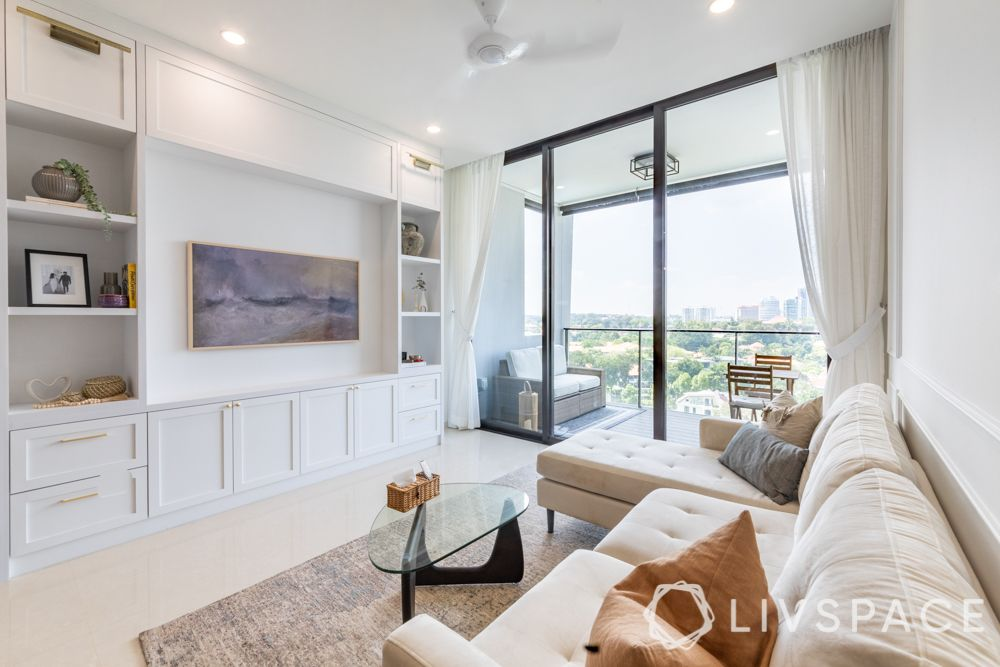 tv-wall-decoration-wall-unit-white-cabinets-drawers-beige-rug-glass-doors-balcony