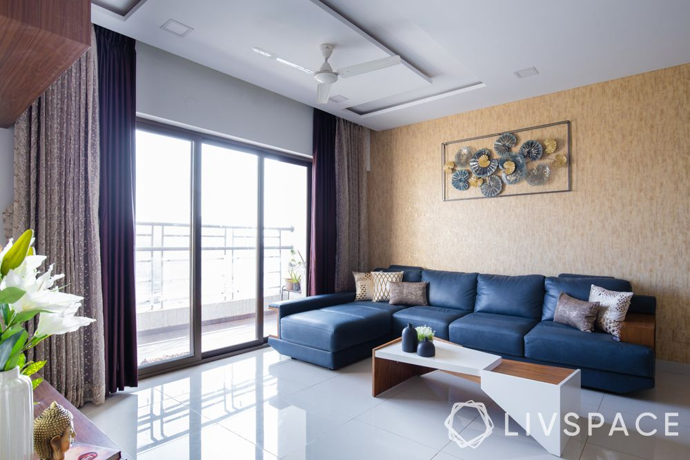 living room designs-clutter free living room-blue L shaped sofa-accent wall