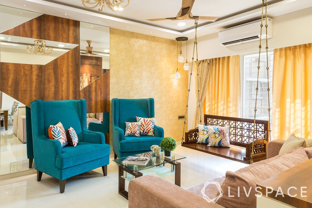 living room designs-blue accent chairs-wooden jhoola-wooden and glass accent wall