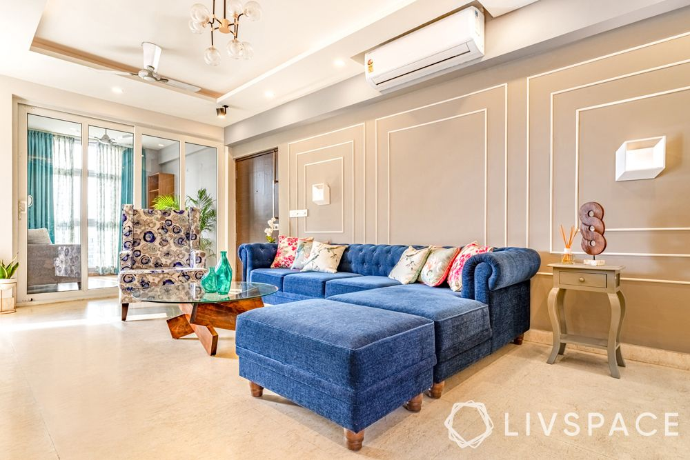 living room designs-blue L shaped sofa-accent chair-wall trims-curvaceous furniture