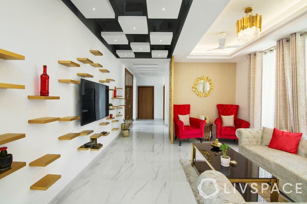 maximalism-living-room-3-bhk-gurgaon-wall-tv-unit-wooden-display-shelves-chandelier-read-seats-white-sofa