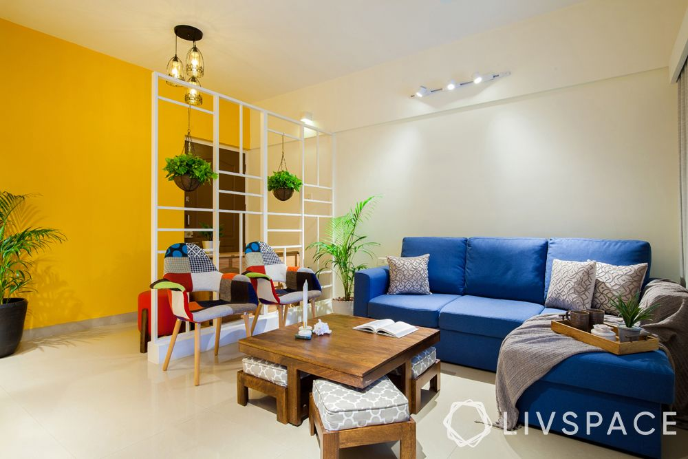 small modern house design-Pune home-yellow wall-metal partition-planters-blue sofa