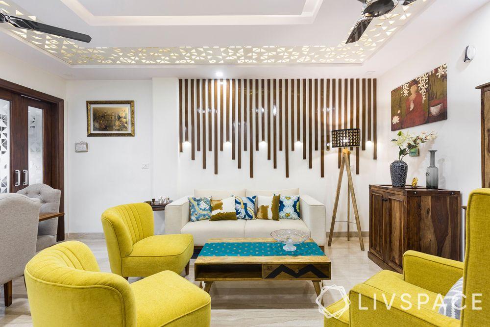 small house design-Delhi homes-wooden pattis on wall-yellow sofa-false ceiling-tripod