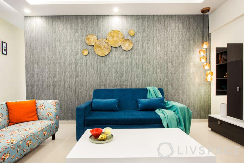 north-facing-house-vastu-plan-dos-don'ts-blue-couch-grey-wall-gold-wall-art